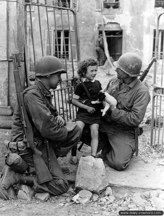 11_juin_1944._le_soldat_roland_bonnel_et_le_sergent_james_devine_reconfortent_un_jeune_enfant_normand_avec_un_chiot_dans_les_bras